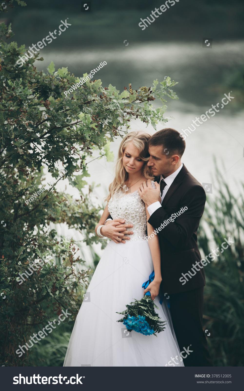 Romantic wedding couple man and wife posing near beautiful lake
