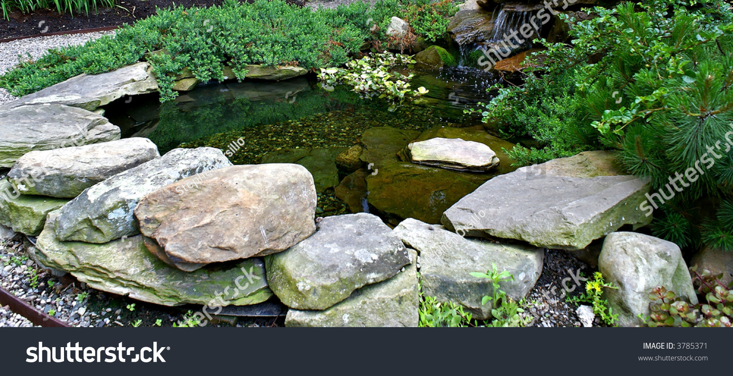 A rock pond surrounded by gravel with water flowing in for Garden pond gravel