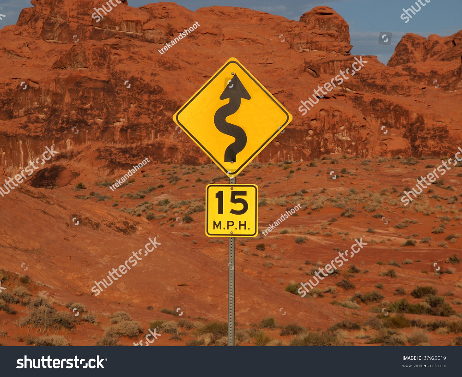 Desert curves ahead highway sign with cliff backdrop. #37929019