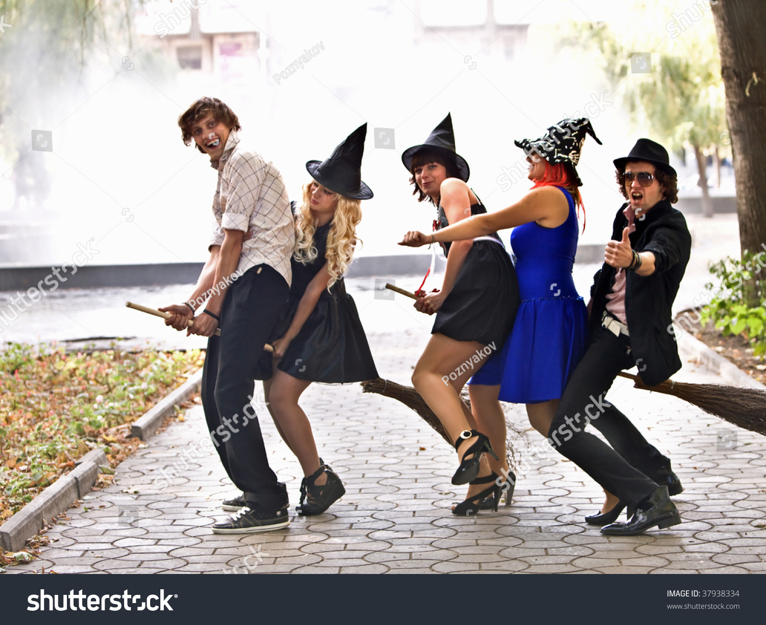 Group Of People On Broom And Halloween Witch Costume In Outdoor ...