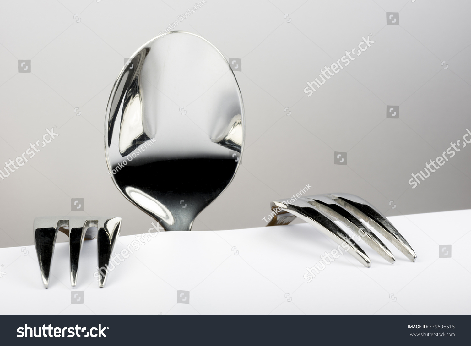 Spoon and two forks formed into conceptual figure #379696618