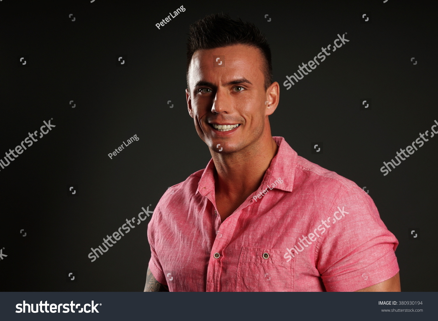 309b1d75 Portrait of young man in pink shirt on gray background, left you can write  some