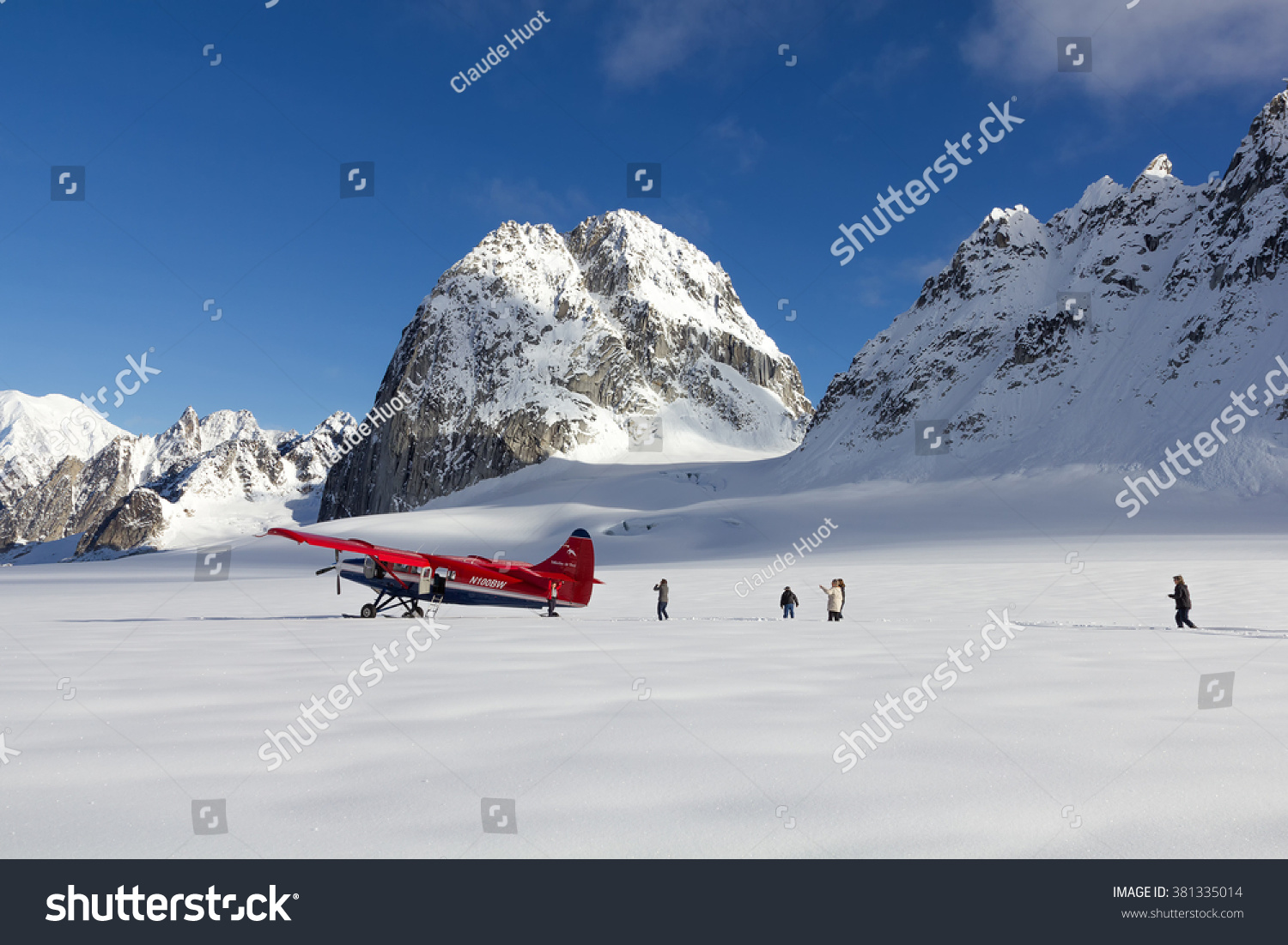 DENALI NATIONAL PARK, ALASKA, USA - SEPTEMBER 14, 2013: Tourists walking in deep snow after plane landing on Pika Glacier near Mount McKinley.