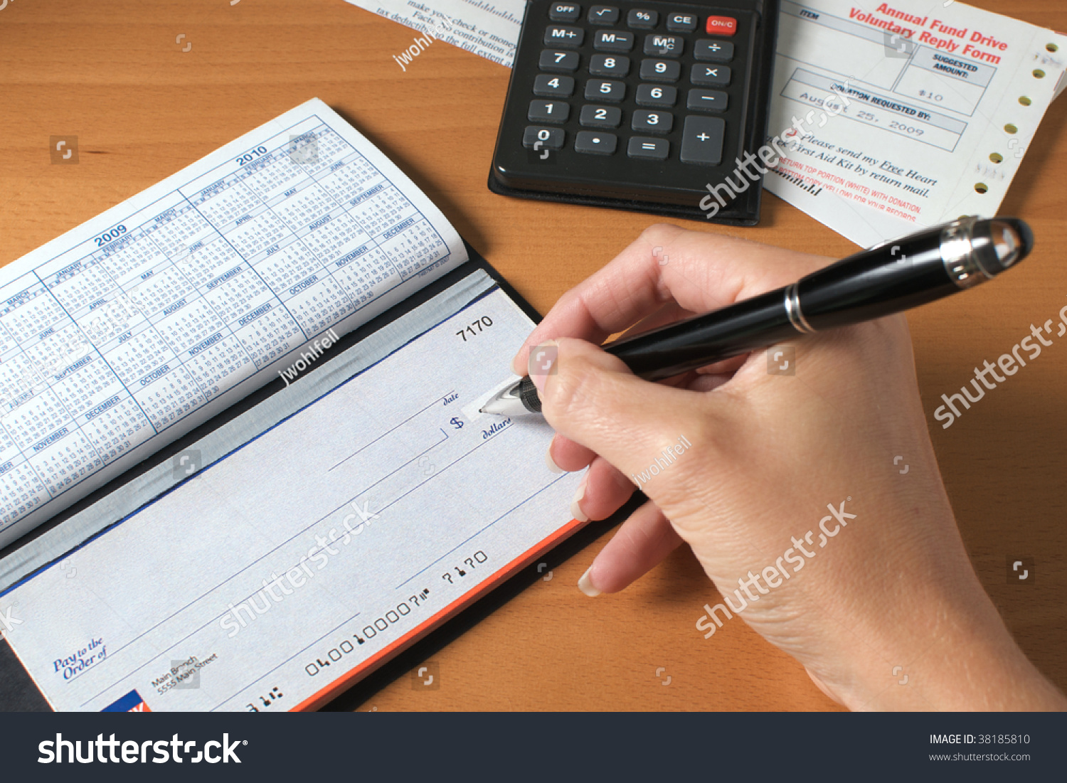 w s hand writing check pay bills stock photo  w s hand writing a check to pay the bills calculator and an invoice on