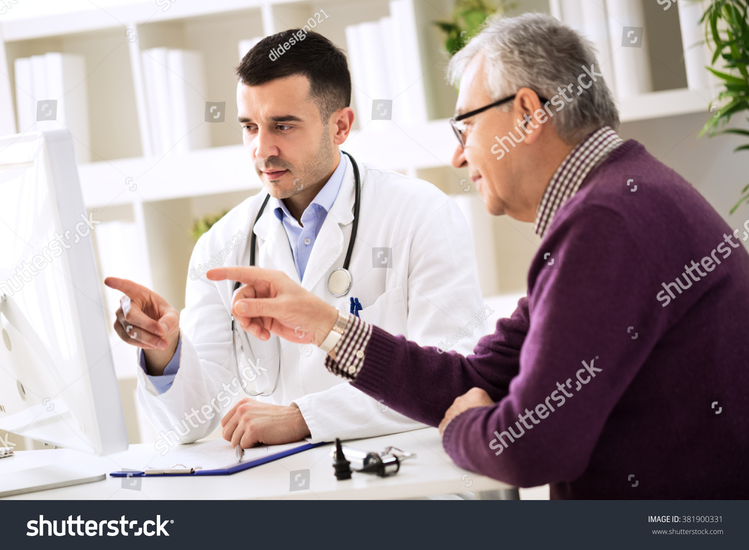 Doctor and senior patient pointing on computer