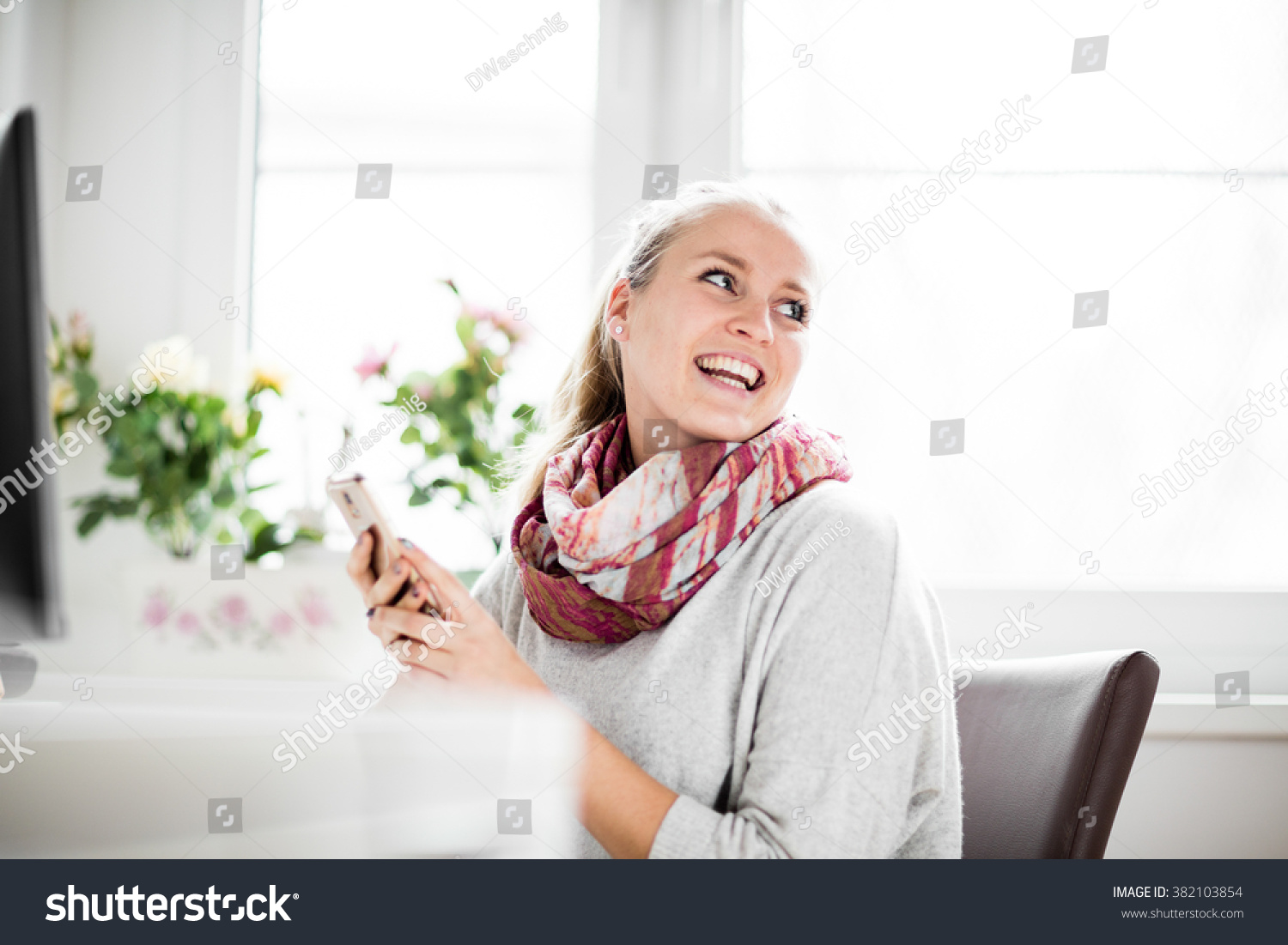 woman working in home office with phone and computer