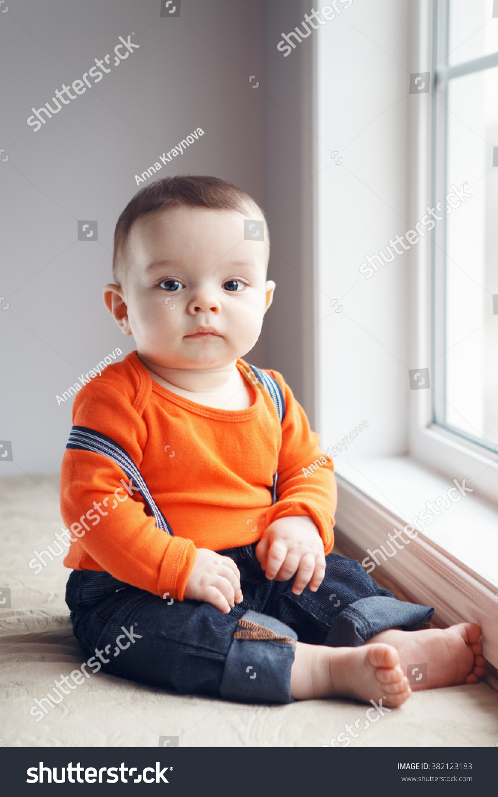9ecdf0127aae Portrait of cute adorable stylish Caucasian baby boy with black eyes in  orange red shirt onesie