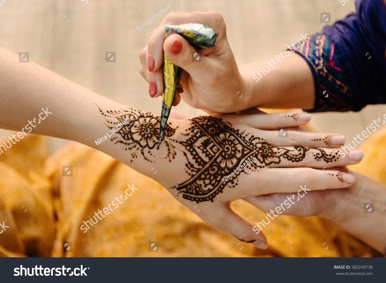 Apply Mehndi Hands : Artist applying henna tattoo on women stock photo