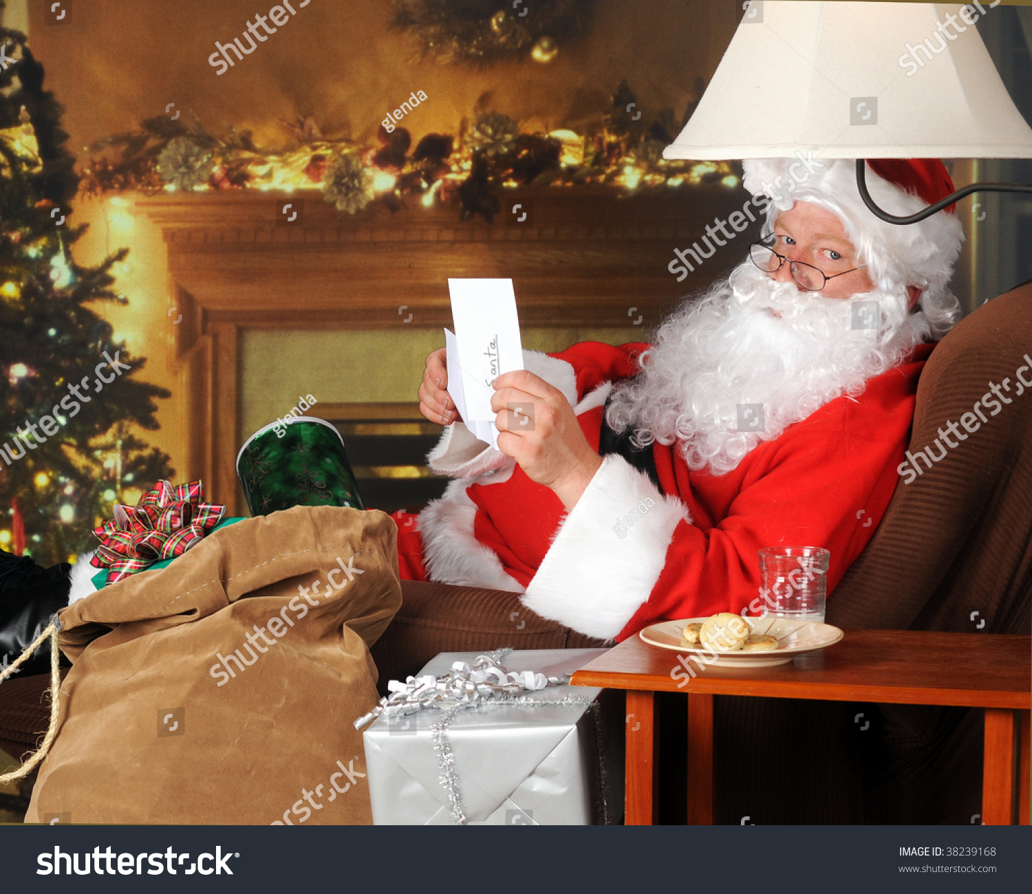 Santa Opening A Note Left By His Cookies And Milk In A Decorated Living Room Stock Photo