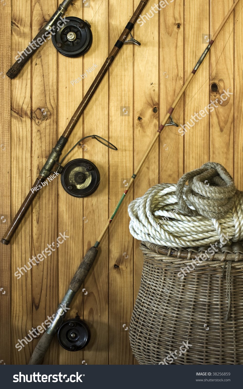 Antique fishing rods on a wooden wall with a wicker for Old fishing rods worth money