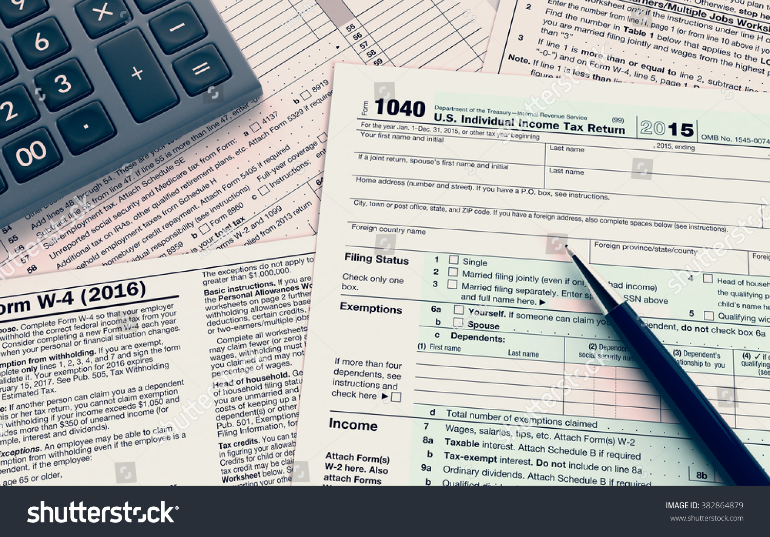 top view of forms for usa taxes, with a pen and an electronic ...