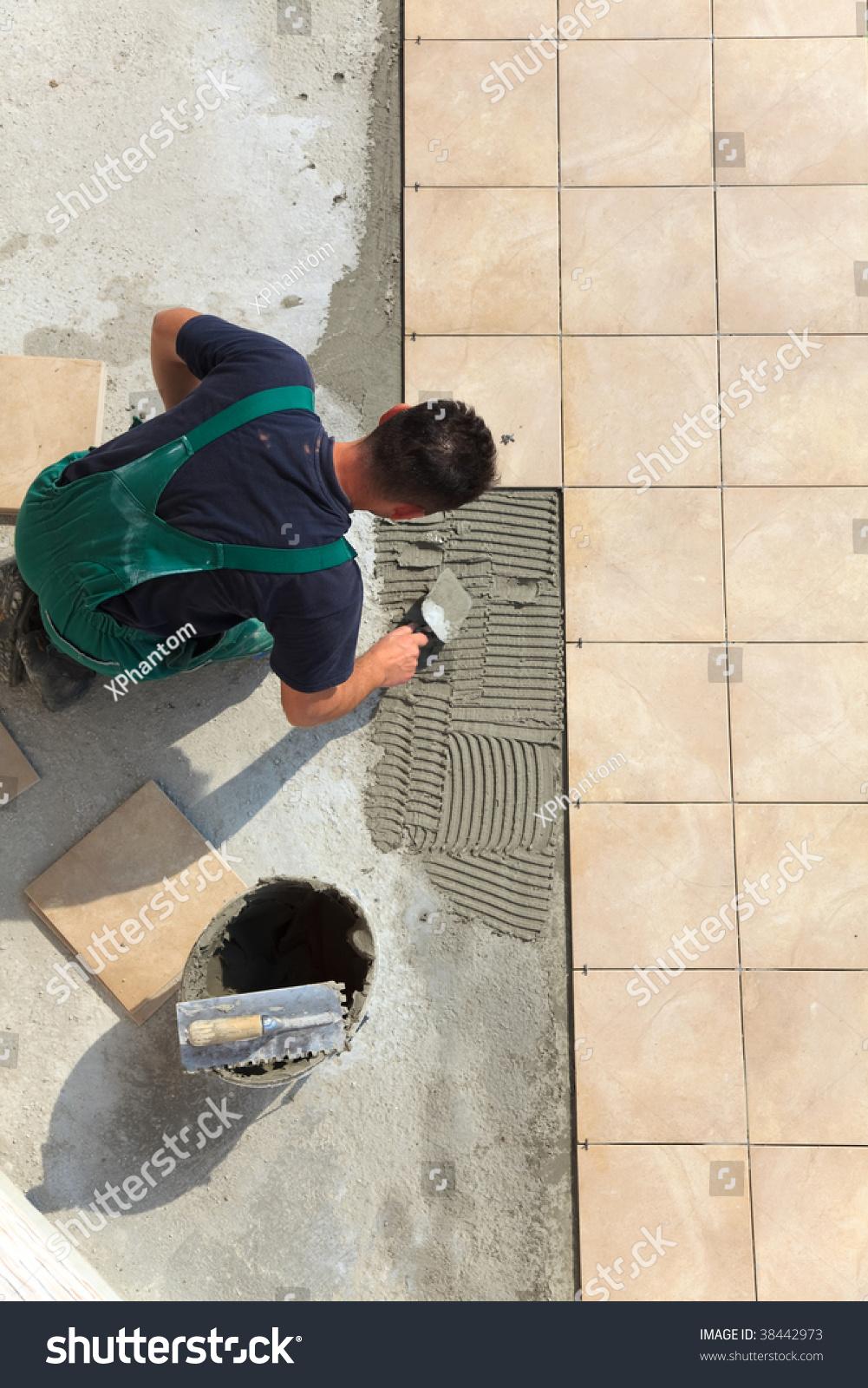 Floor tiles installation man installs ceramic stock photo 38442973 floor tiles installation man installs ceramic tile doublecrazyfo Gallery