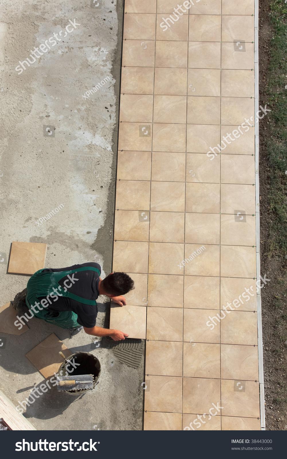 Floor tiles installation man installs ceramic stock photo 38443000 floor tiles installation man installs ceramic tile doublecrazyfo Gallery