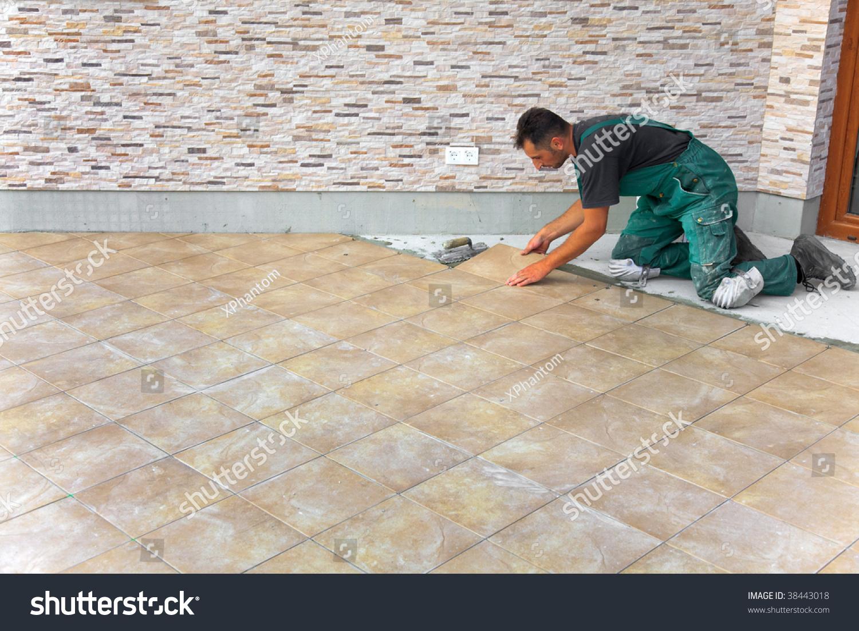 Floor tiles installation man installs ceramic stock photo 38443018 floor tiles installation man installs ceramic tile doublecrazyfo Gallery
