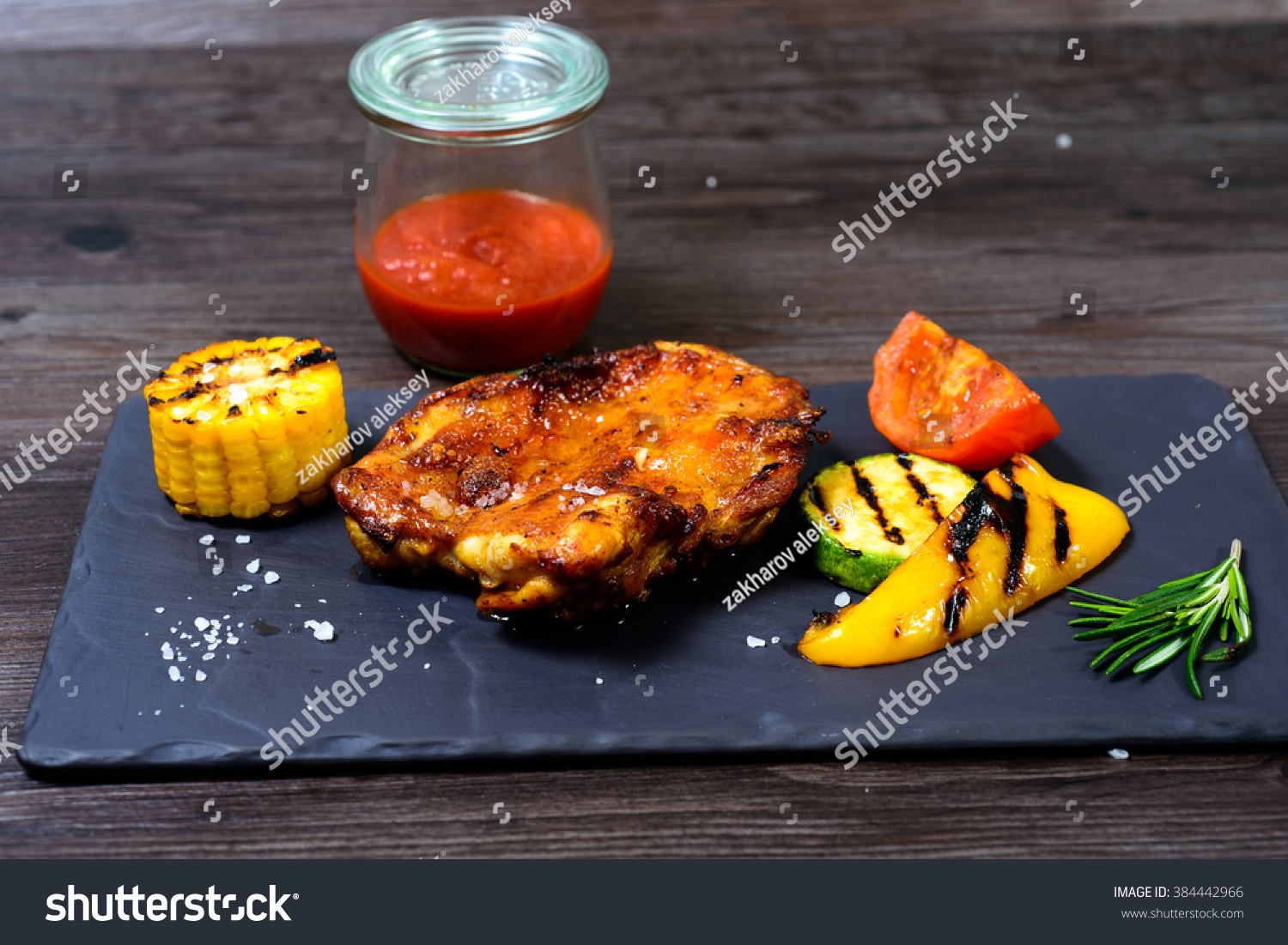 juicy grilled chicken with vegetables on a basalt slab #384442966