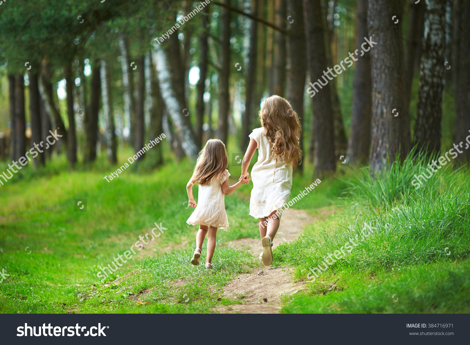 Two sisters run through the forest holding hands Summer sunny day and girls in light dresses Beautiful long hair in a child
