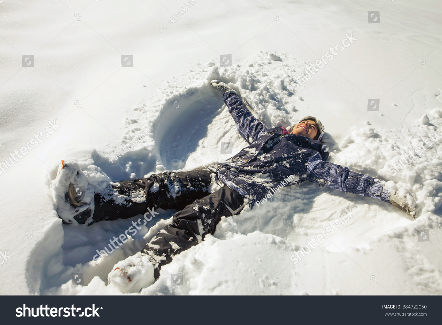 Happy woman making snow angel in the ski funny