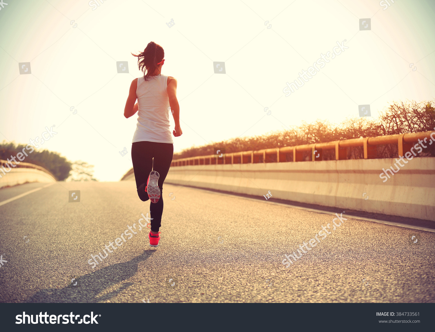 young fitness woman trail runner running  on city road #384733561