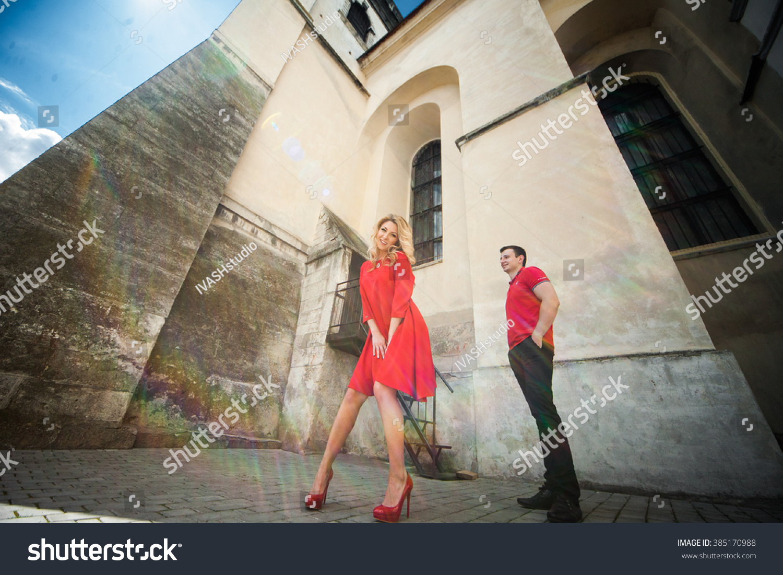 Beautiful sexy blonde bride & groom posing near church wall