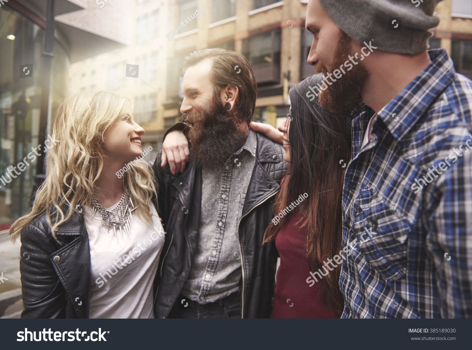 Four hipsters meeting in the city centre #385189030