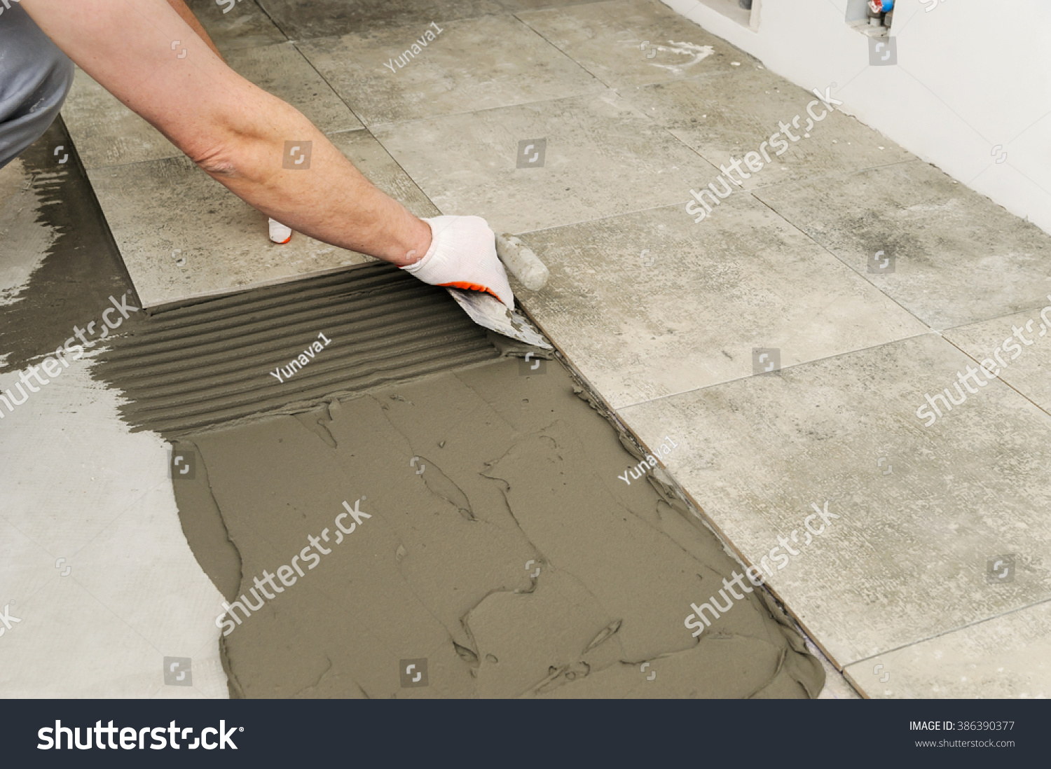Laying ceramic tiles troweling mortar onto stock photo 386390377 laying ceramic tiles troweling mortar onto a concrete floor in preparation for laying floor tile dailygadgetfo Gallery