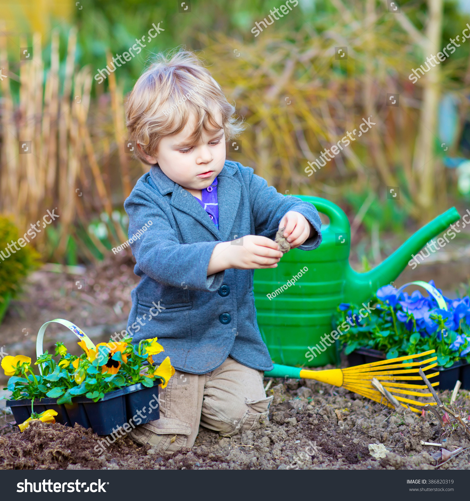 active adorable kid boy helping with gardening in spring garden funny child planting flowers