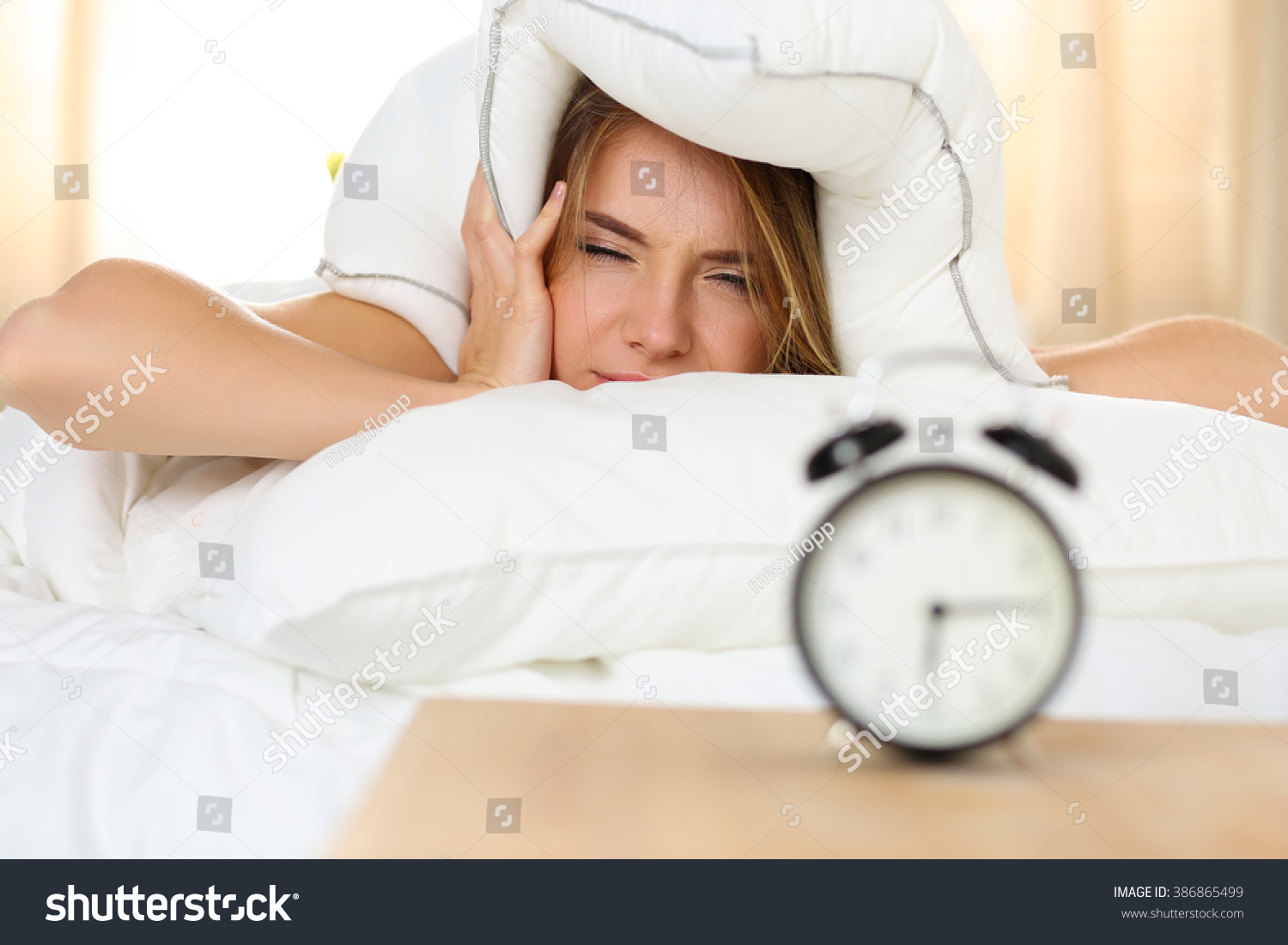 Young Beautiful Blonde Woman Lying In Bed Suffering From Alarm Clock Sound  Covering Head And Ears