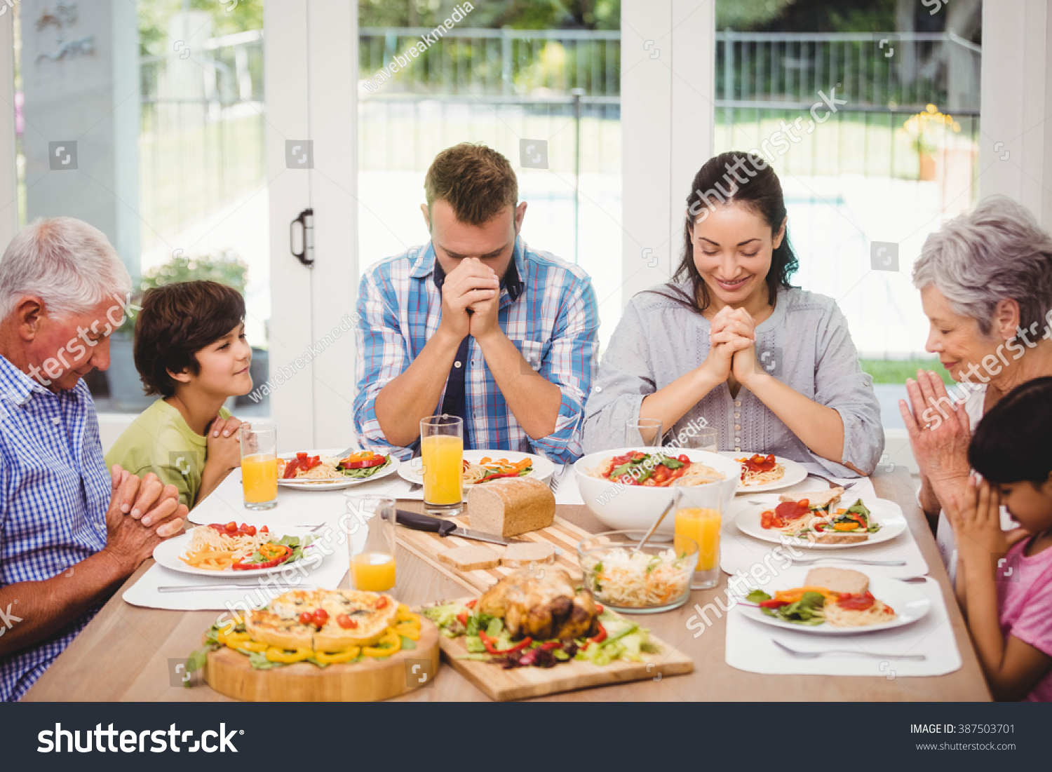 Family Sitting At Dining Table And Praying Together Before ...
