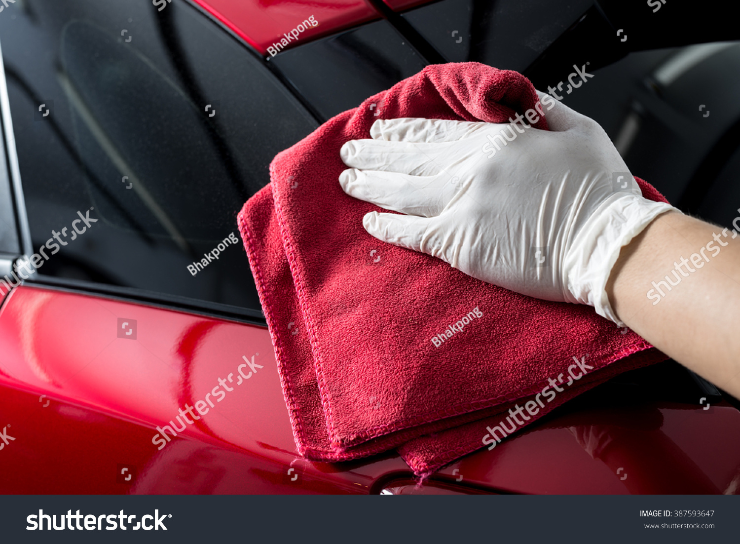 Car detailing series Worker cleaning red car