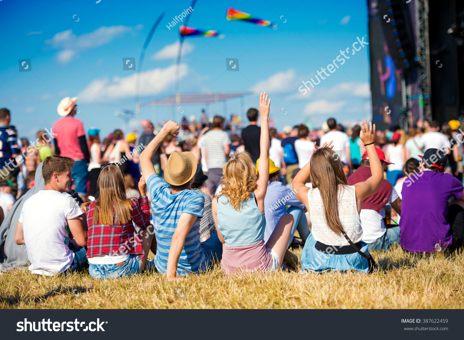 Teenagers, summer music festival, sitting in front of stage #387622459