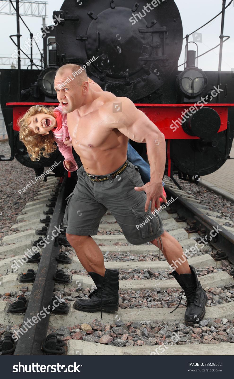 Strong Shirtless Man Saving Girl On Railroad Stock Image