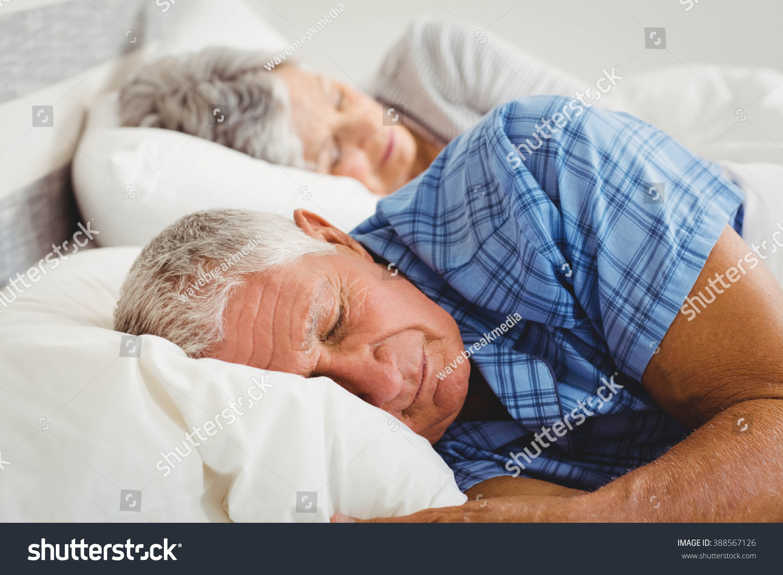 nude couple sleeping on bed