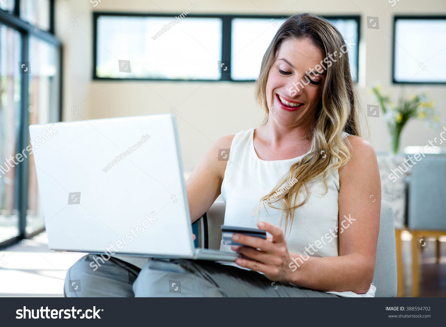 Smiling woman sitting on couch on stockfoto 388594702 shutterstock - Voorbeeld volwassene kamer ...