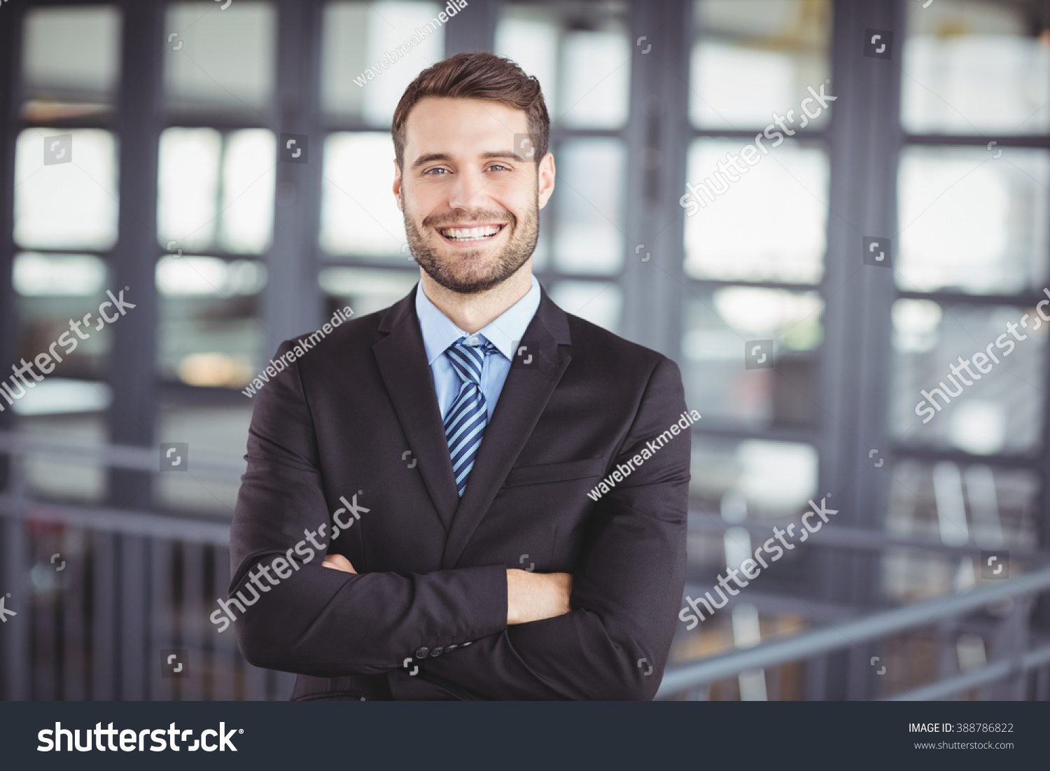Portrait of happy businessman with arms crossed standing in office #388786822