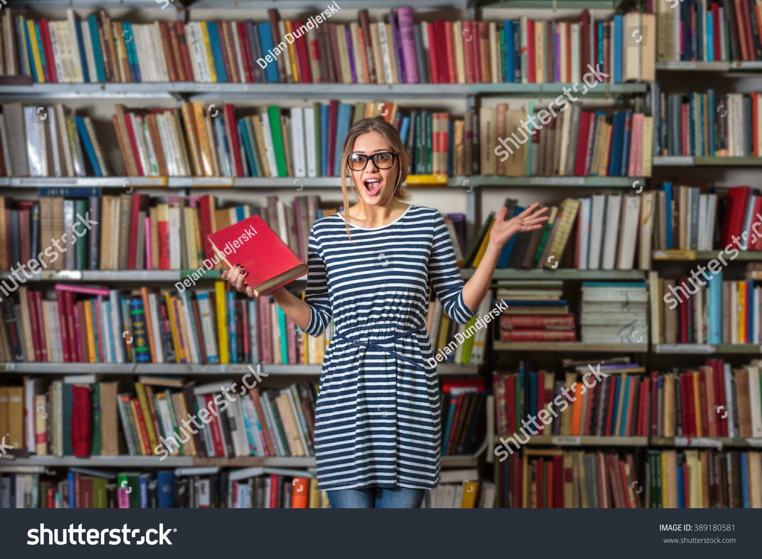 College Student Standing In Front Of Bookshelf