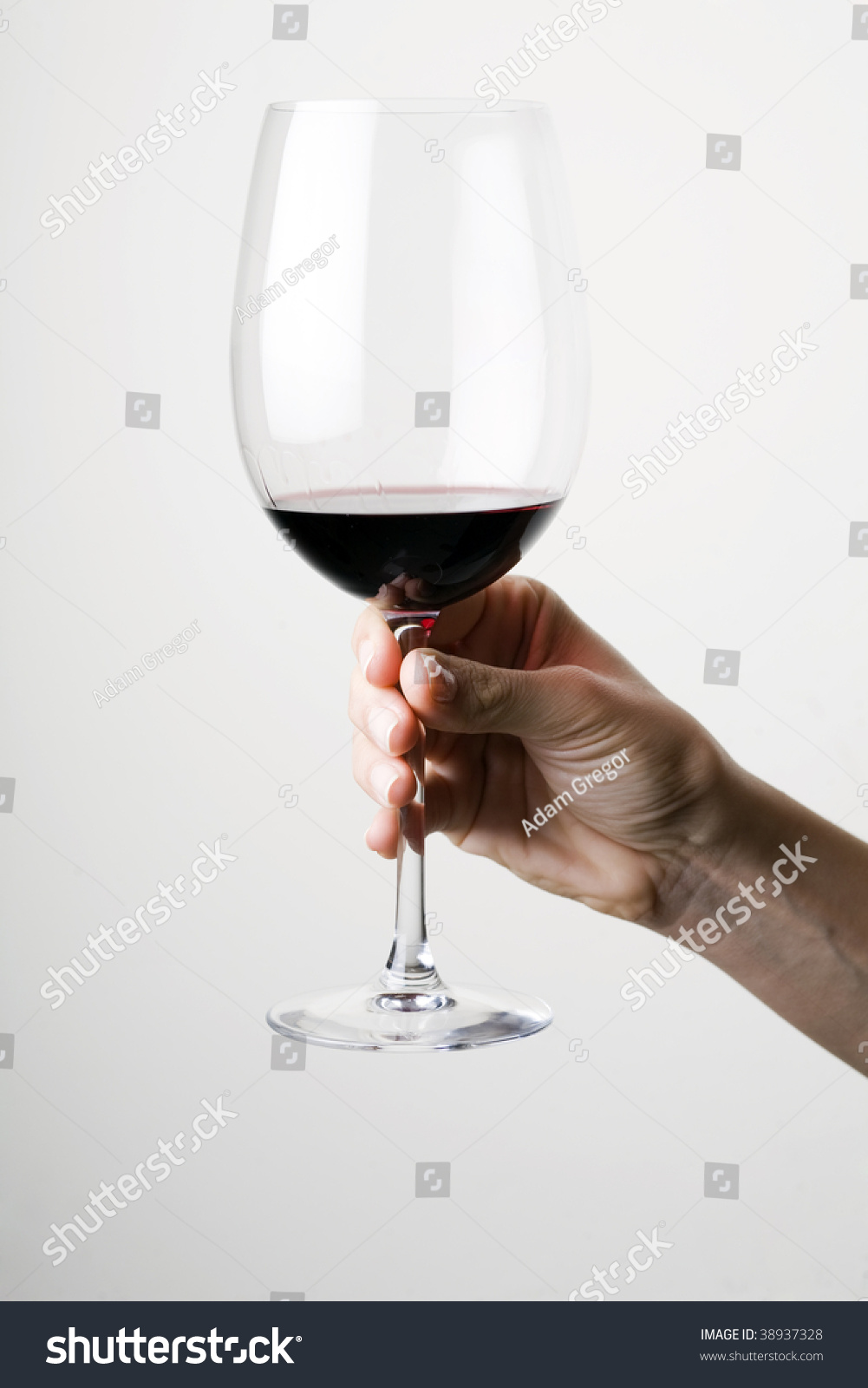 Hand Holding A Glass Of Red Wine Stock Photo 38937328