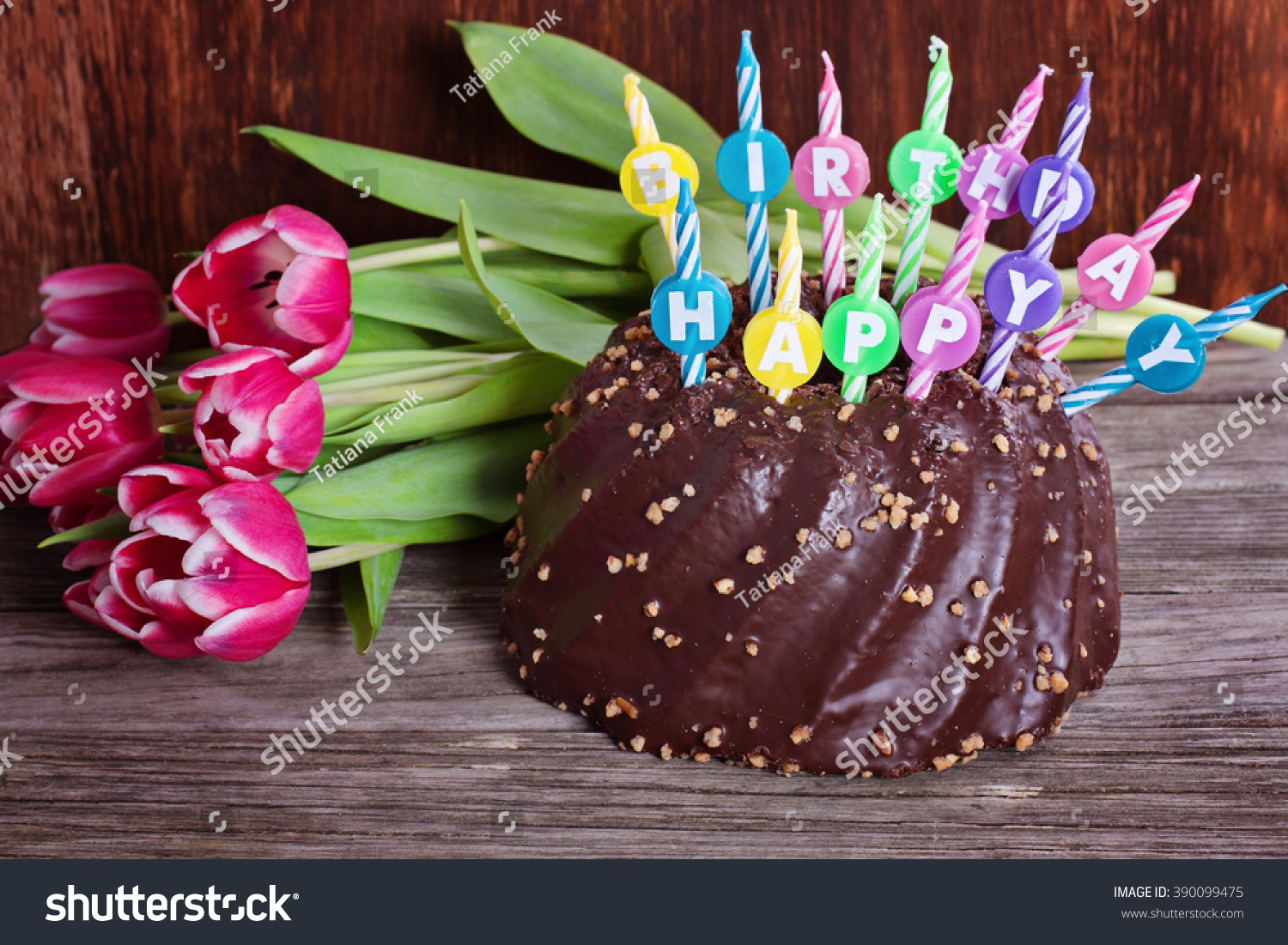 Chocolate Birthday Cake With Happy Candles And Tulips On Wooden Background