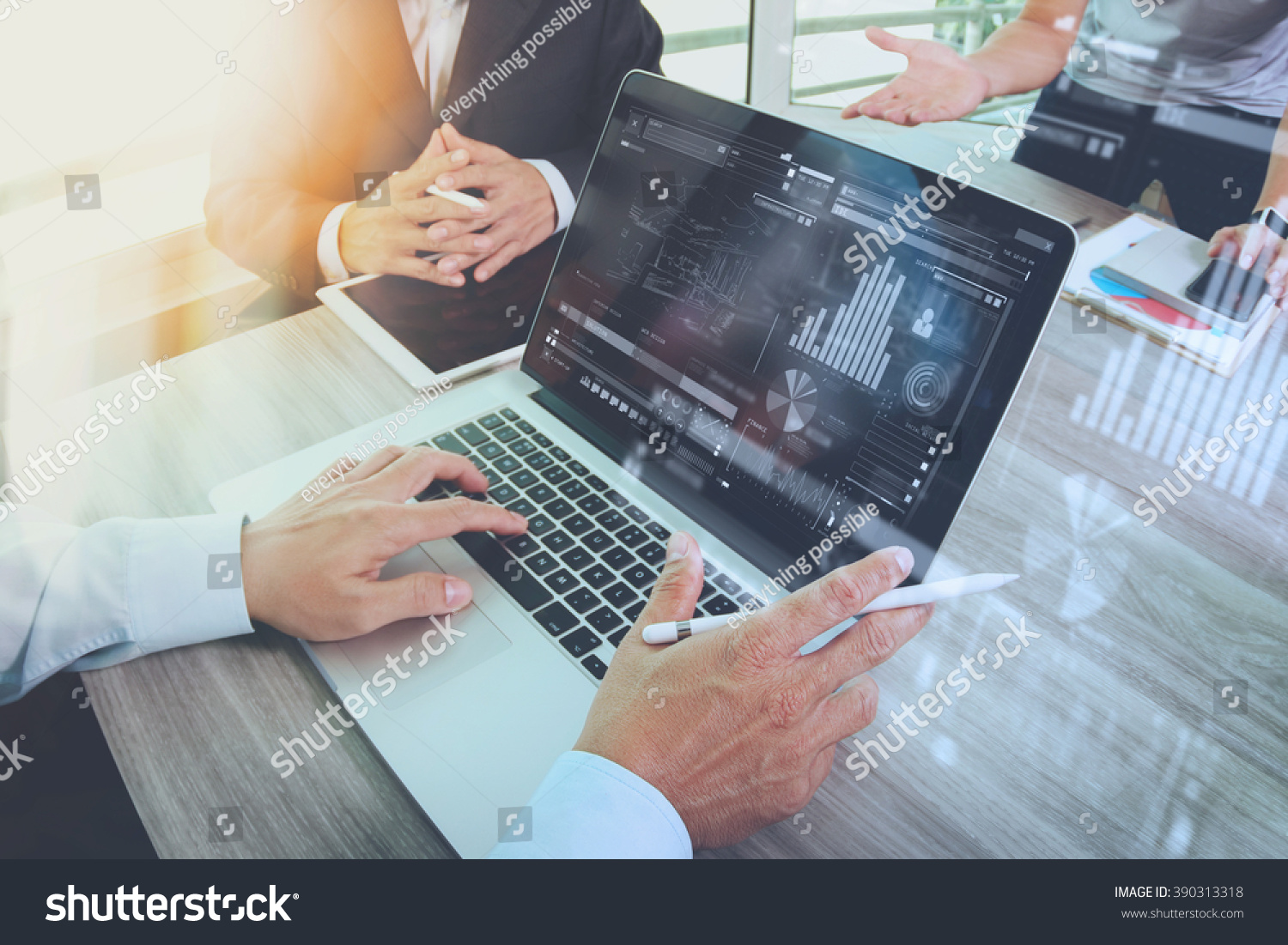 business documents on office table with smart phone and laptop computer and graph financial with social network diagram and three colleagues discussing data in the background   #390313318