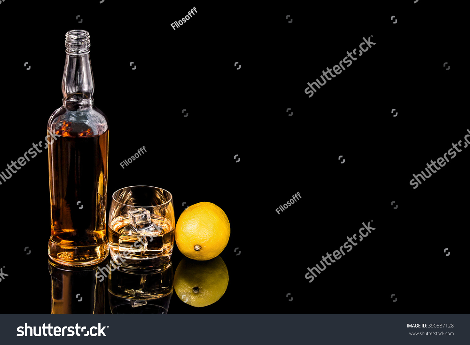 Bottle and a glass of whiskey with ice and  lemon on a black background #390587128
