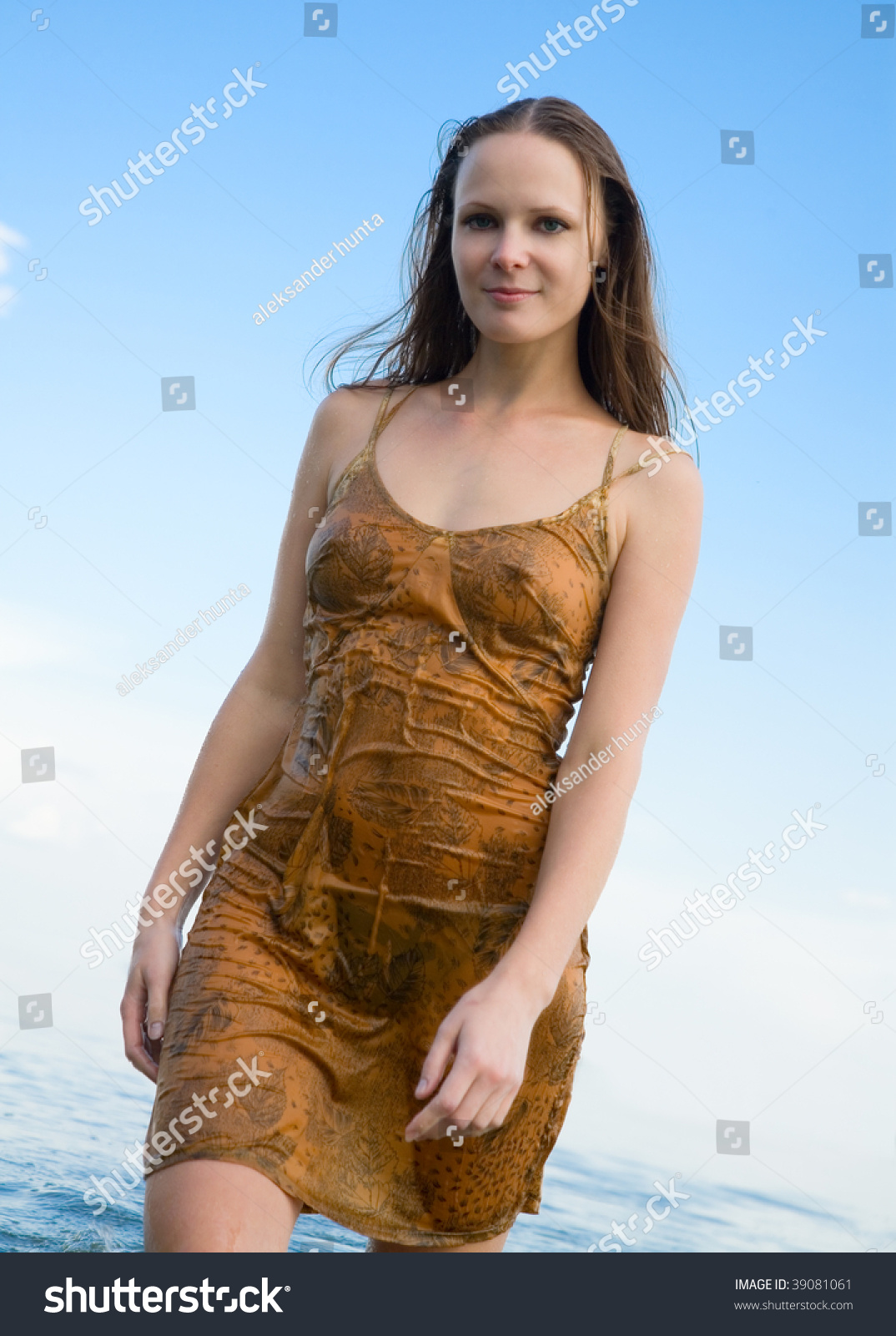 Beautiful Girl In Wet Dress Goes On Shore Stock Photo.