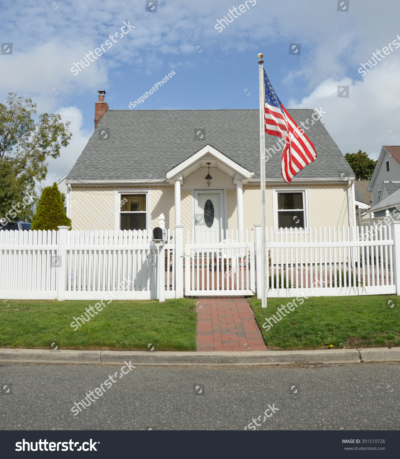 Residential Bungalow Part - 43: American Flag Pole Suburban Bungalow Style Home White Picket Fence Blue Sky  Clouds Day Residential Neighborhood