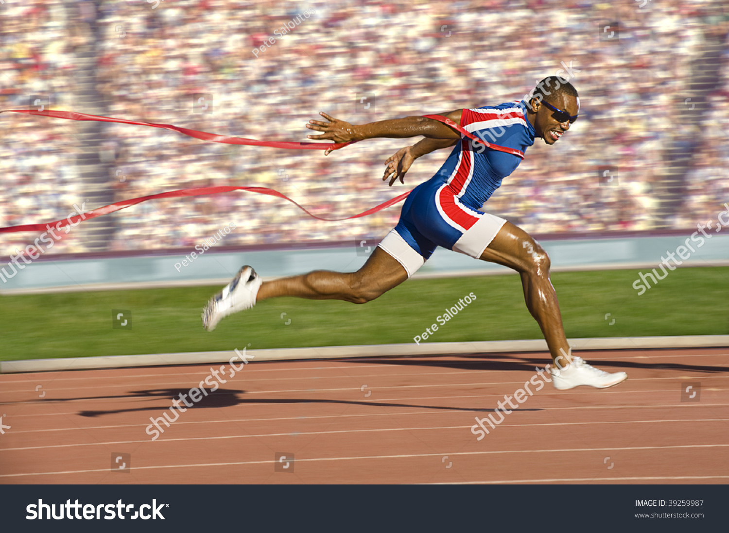 African American Sprinter Crossing Finish Line Stock Photo