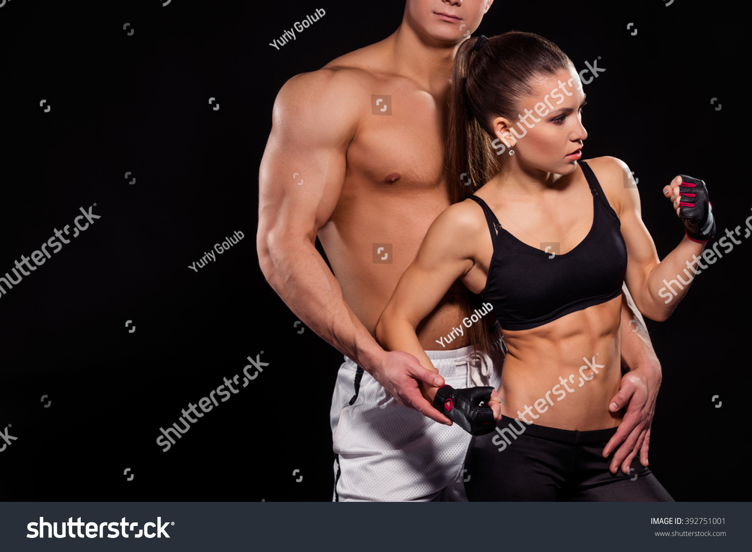 Bodybuilder touches girl flexing bicep. Girl flexing arm near guy. Learning  how to pose