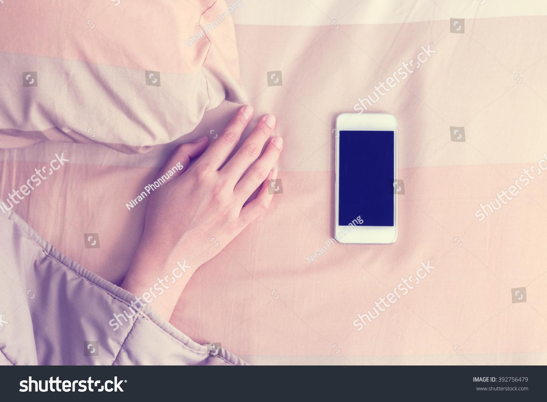 Woman hand under blanket being woken by mobile phone in bedroom