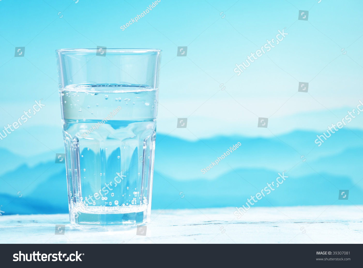 Glass Mineral Water Against Mountain Landscape Stock Photo