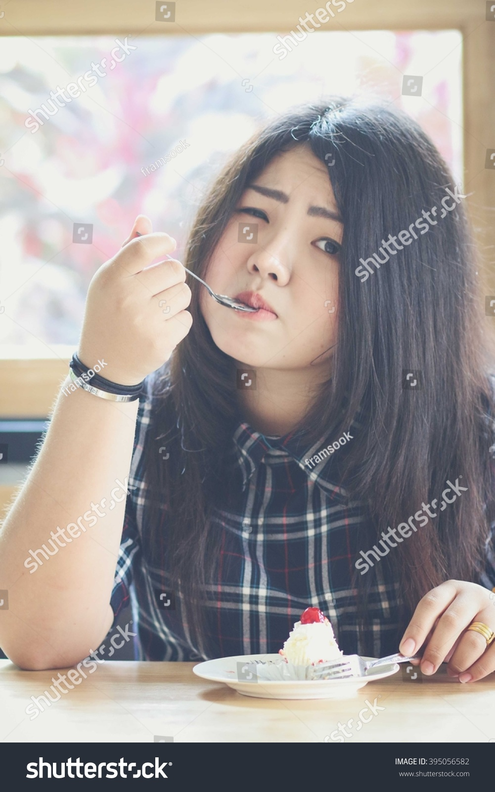 chubby young asian woman eating cake stock photo (royalty free
