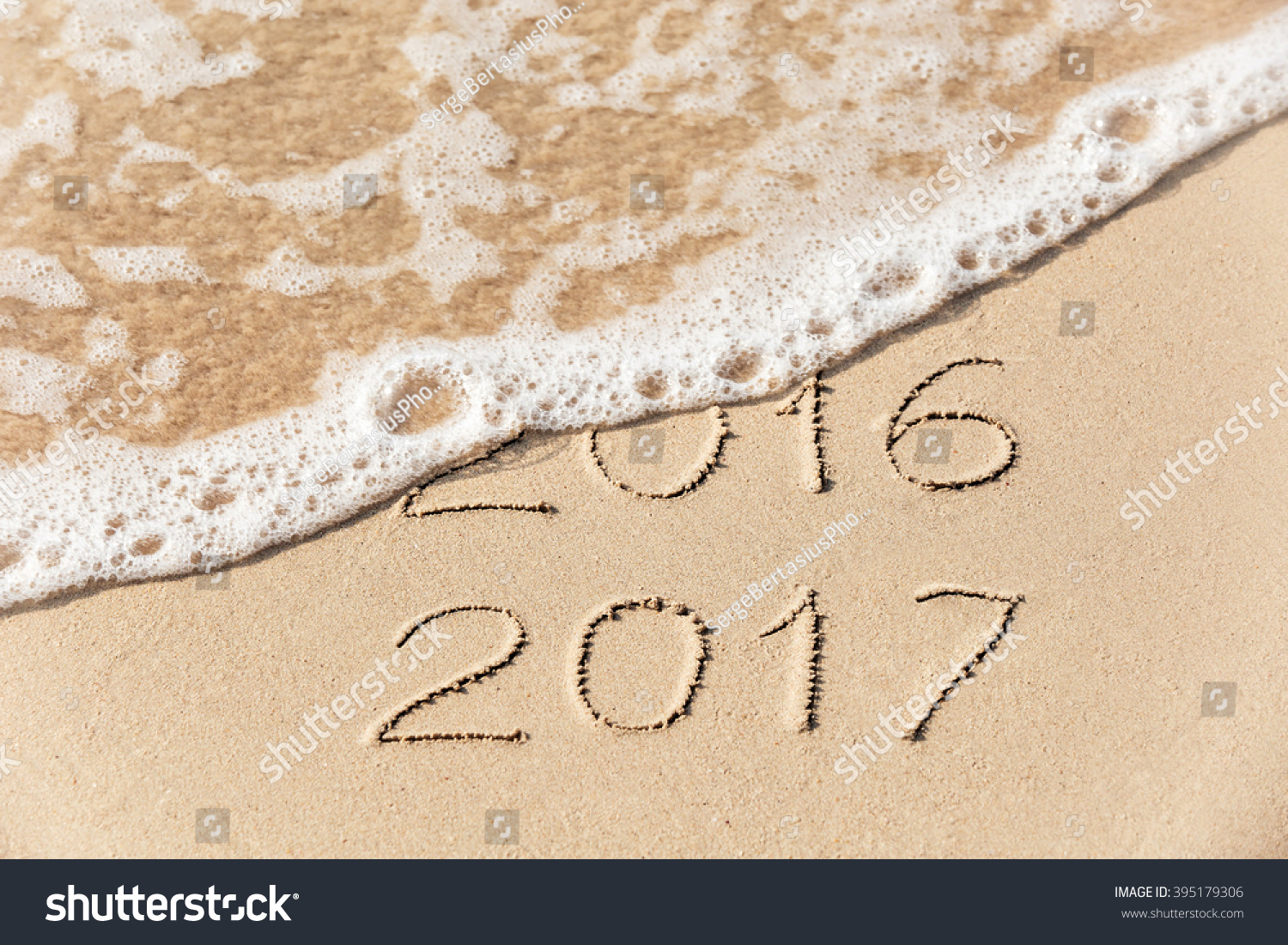 2016 2017  inscription written in the wet yellow beach sand being washed with sea water wave. Concept of celebrating the New Year at some exotic place #395179306