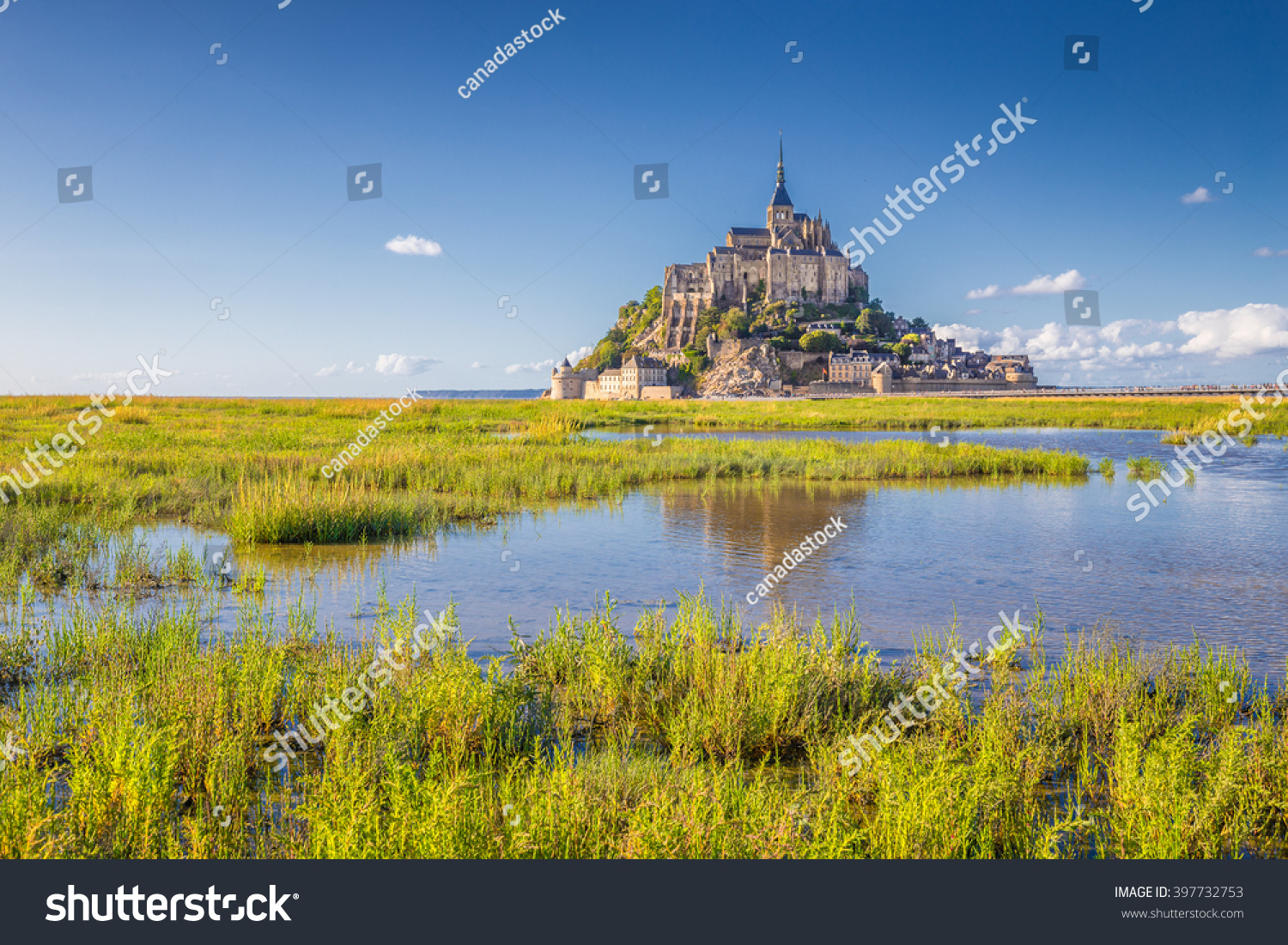 Panoramic view of famous historic Le Mont Saint-Michel tidal island on a sunny day with blue sky and clouds in summer Normandy northern France