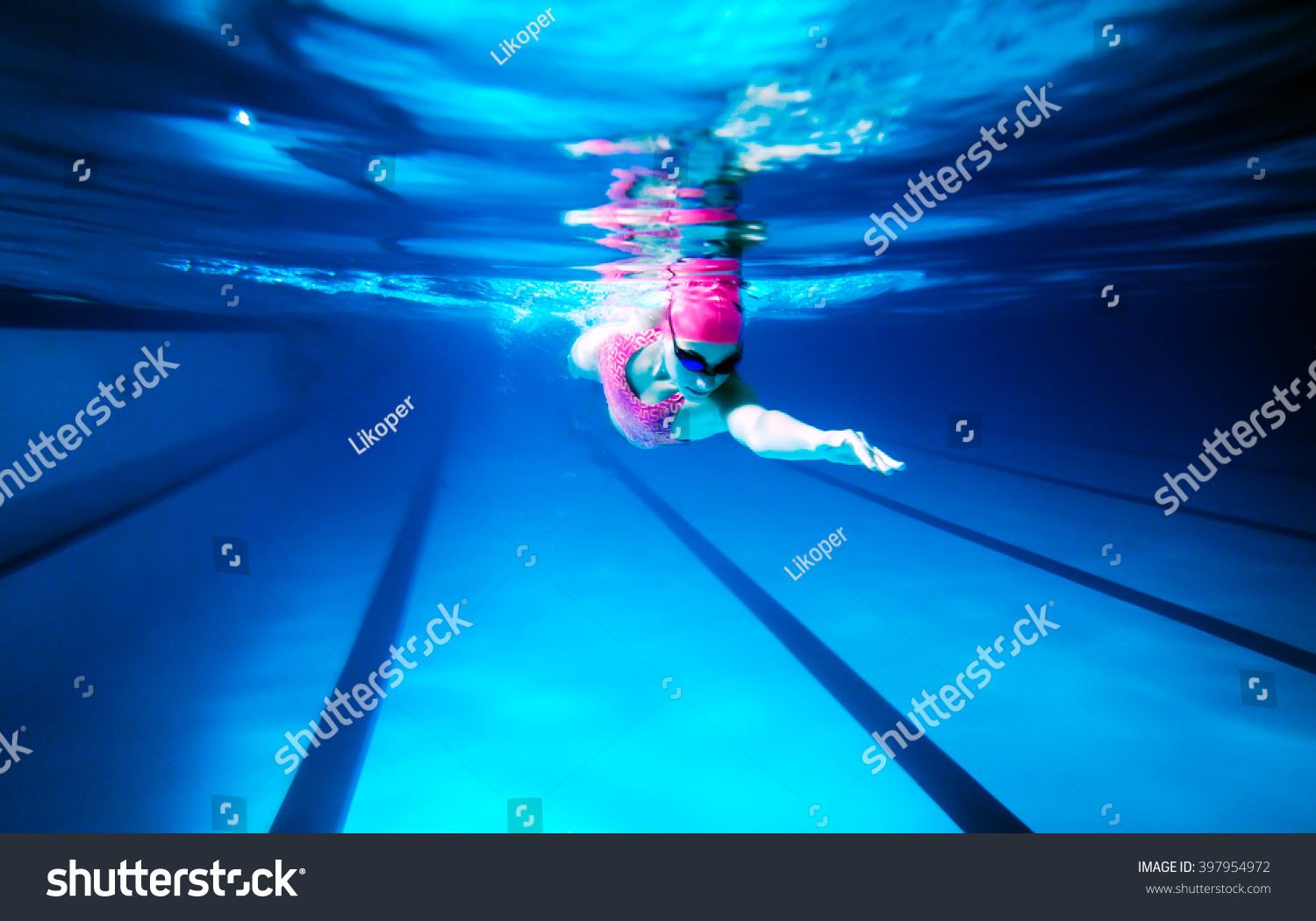 woman swimming freestyle under water shoot of a woman swimming freestyle in olympic pool