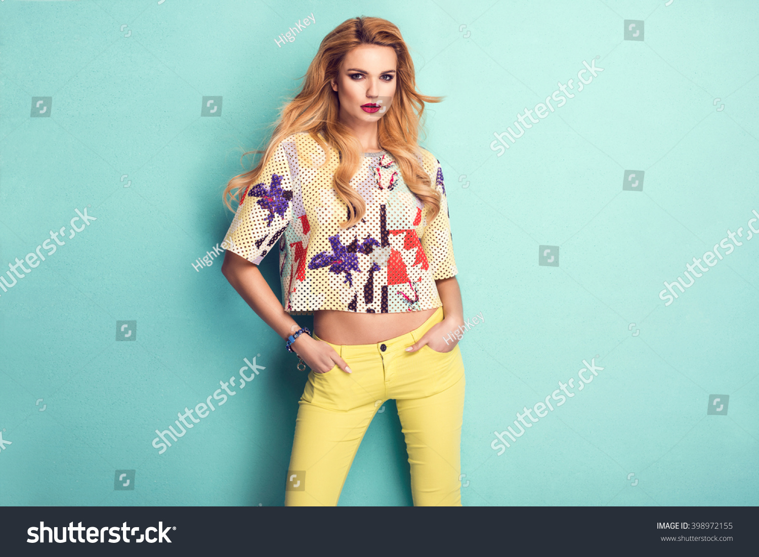 Beautiful woman wearing nice clothes handbag posing on turquoise background Fashion spring photo Bright colors